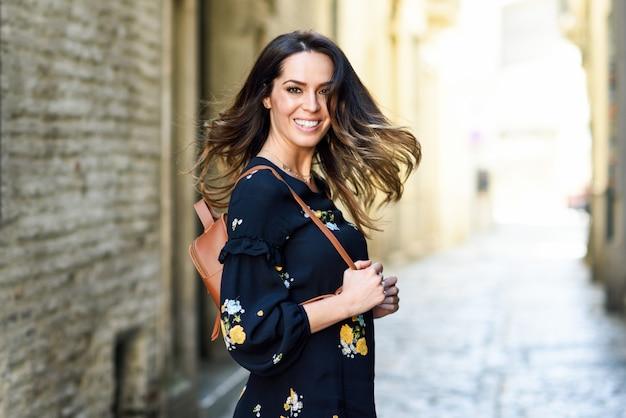 Молодая женщина, перемещение ее длинные волосы в городской фон.