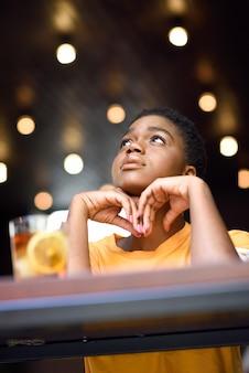 冷たいお茶のグラスを取って非常に短い髪の若い黒人女性
