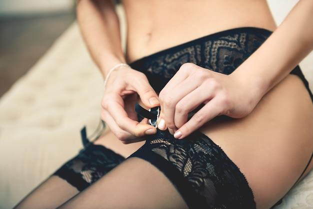 ベッドに横たわっているランジェリーのセクシーな若い女性