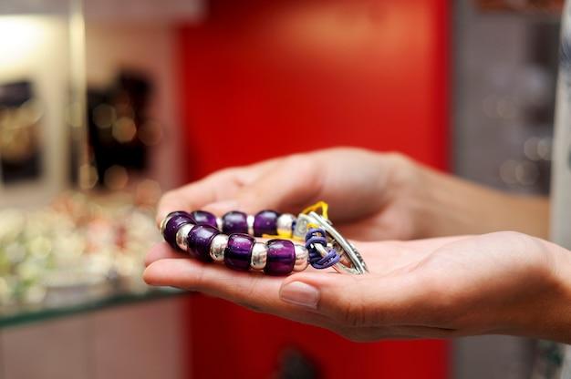 宝石店でブレスレットを取っている女性の手