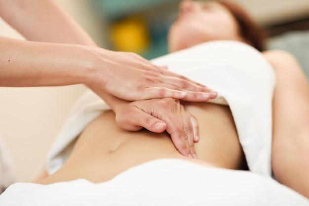 セラピストは腹に圧力をかけます。女性の腹部をマッサージする手。