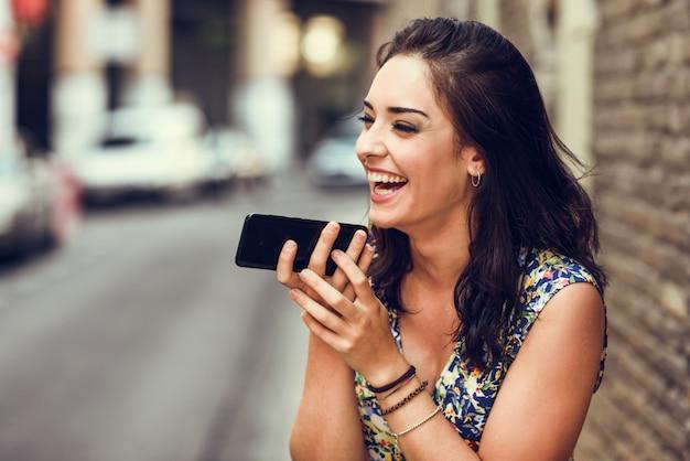 彼女のスマートフォンで音声メモを記録する若い女性の笑みを浮かべてください。