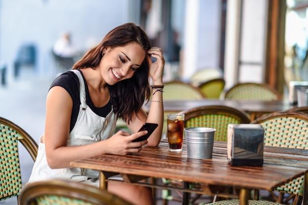 スマートフォンを使用して都市のカフェに座っている青い目を持つ女性の笑みを浮かべてください。