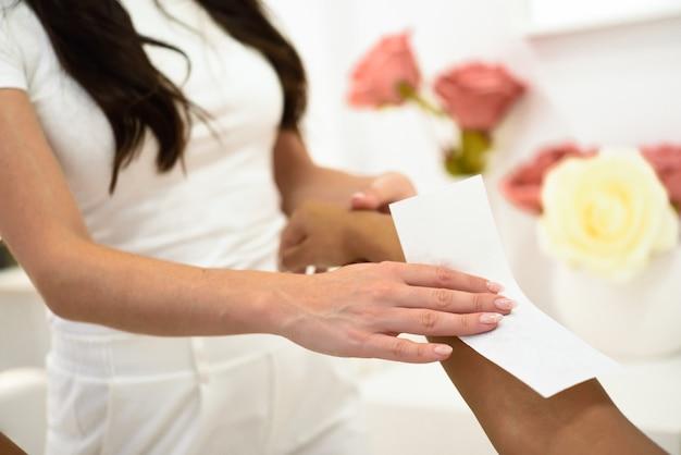 ワックスストリップを適用する腕に脱毛手順を持つ女性