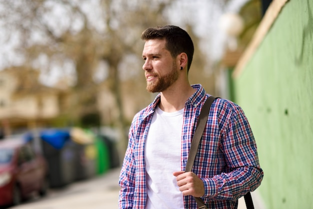 魅力的な若い男が都市の背景に立っています。ライフスタイルのコンセプトです。