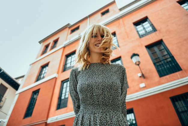 都市の背景に髪を移動すると幸せな若い女。