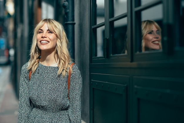 Усмехаясь молодая белокурая женщина стоя на городской предпосылке.