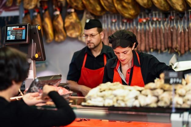 Мясники, сопровождающие покупателя в мясной лавке