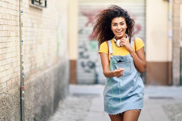 野外を歩いているヘッドフォンを持つ若いアフリカ人女性