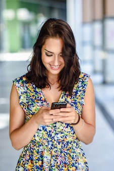 彼女のスマートフォンを屋外で使う若い女性の笑みを浮かべてください。