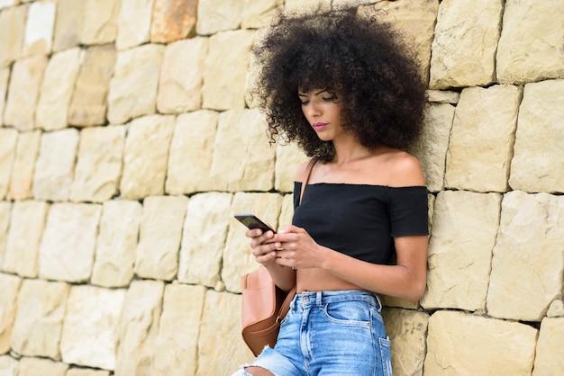 彼女のスマートフォンを屋外で見ている深刻な黒人女性