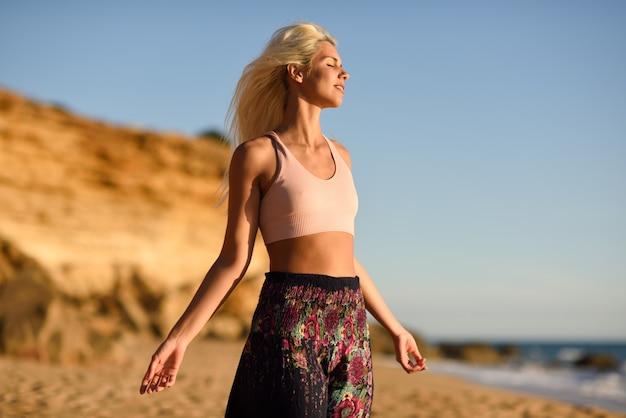 美しいビーチで夕日を楽しむ女性