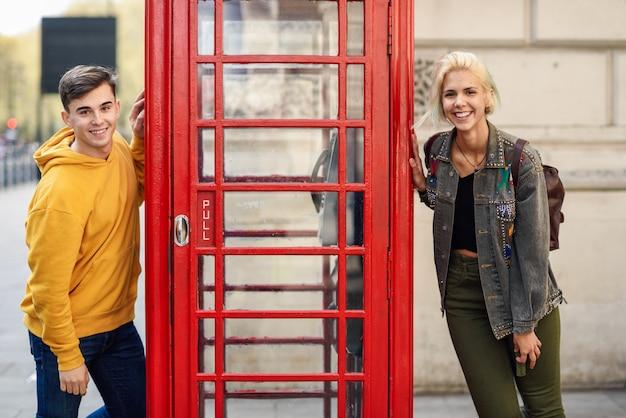 古典的なイギリスの赤い電話ボックスの近くの友人の若いカップル