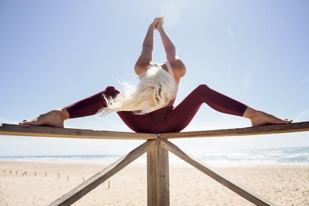 白人の金髪女性がビーチでヨガの練習