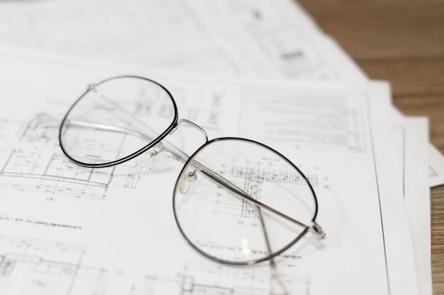 テーブルの上の眼鏡をかけた建築平面図
