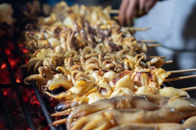 中華街タイの屋台の食べ物を棒でイカのグリル