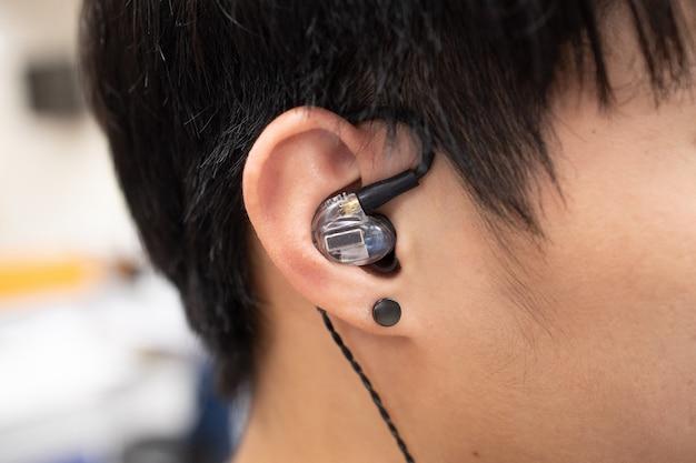 彼の耳にイヤホンやイヤホンでアジア人男性の耳にクローズアップ