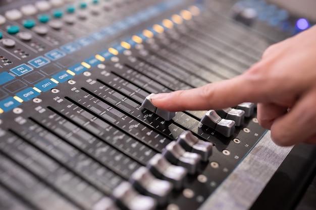 イベントホールでサウンドミュージックミキサーのコントロールパネルを使用している手