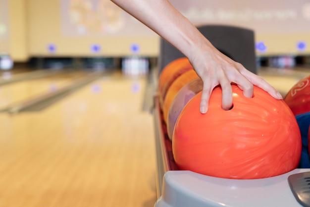 ボーリング場に対してスタックからボウリングボールを持つ女性の手にクローズアップ