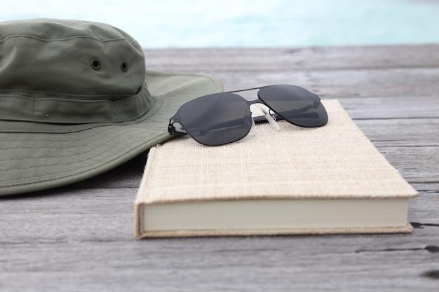 Концепция путешествия и отдыха камеры солнцезащитные очки и книги на деревянный пол