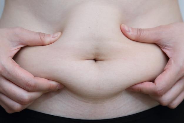 Женщина схватила свой толстый живот