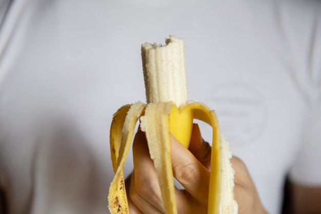 かまれたバナナを保持している男