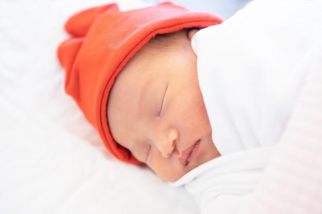 オレンジ色の帽子と毛布の上に寝ている生まれたばかりの赤ちゃん