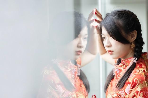 中国の新年のお祝いのチャイナドレスでアジアの女性の肖像画
