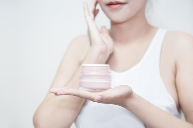 Женщина держит в руках увлажняющий крем и наносит крем на лицо