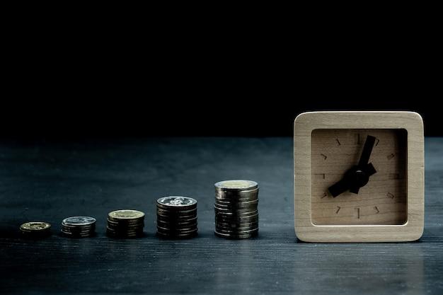 木製時計とコインのスタックからの成長グラフ