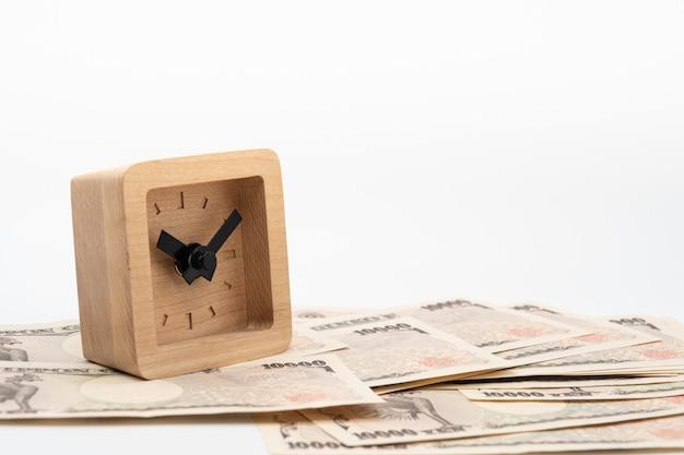 日本の通貨円お金紙幣の小さな正方形の木製時計を閉じます。日本経済と投資。
