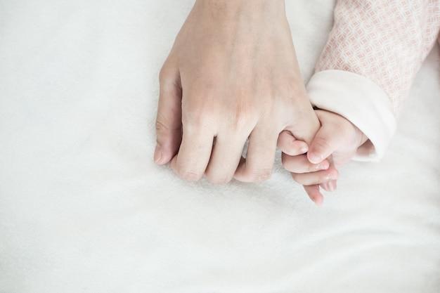 新しい生まれた赤ちゃんの手は、お母さんの指を保持:愛の概念は、世話をする親の関係