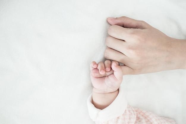 新しい生まれた赤ちゃんの手がお母さんの指を保持:愛の概念は、世話をする親の関係