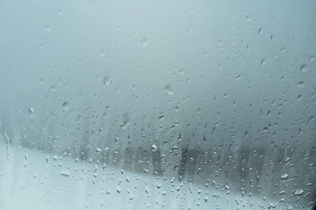 Капли воды на оконное стекло от конденсата. капли дождя на фоне оконного стекла