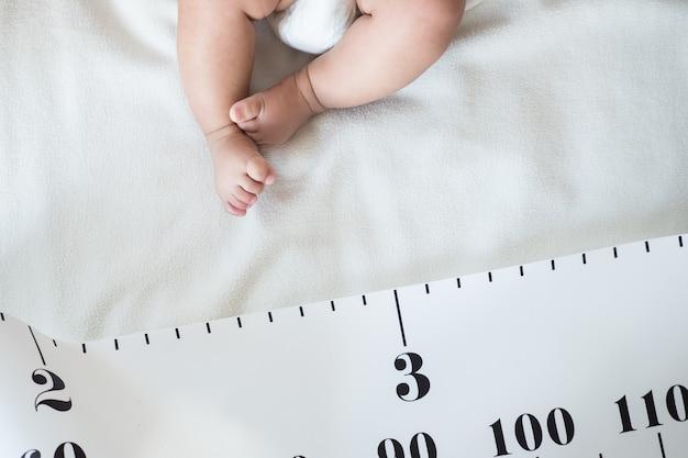 Детская нога и рулетка: концепция роста, роста, развития ребенка