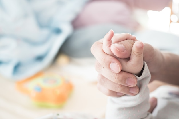 新しい生まれたベビーの手がお母さんの小さな指を保持:愛の概念は、世話をする