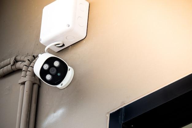 壁の白い監視カメラ、コンセプトのセキュリティ都市。