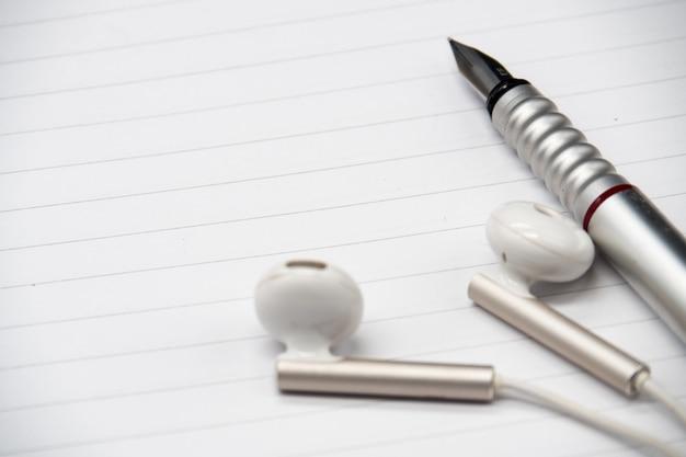 インクペンとヘッドフォン、および木製の背景の空白のノートブックを閉じます。