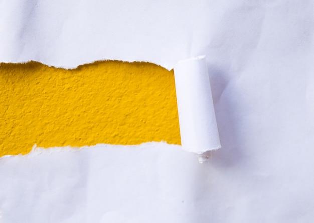 黄色の紙の破れた壁