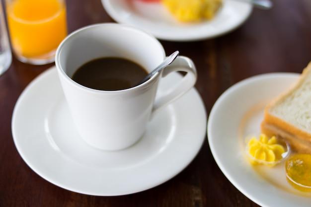 コーヒーと朝食を木製のテーブルに設定