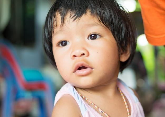 アジアの女の赤ちゃんの顔を閉じる