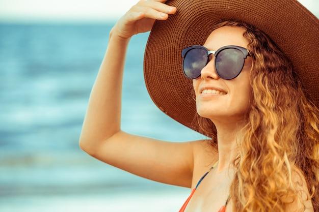 夏休みのビーチで幸せな若い女。