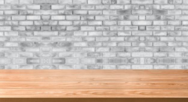 レンガの壁の前に木製のテーブルは、背景をぼかし。