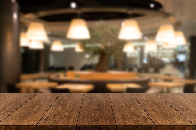 モダンなレストランの背景をぼかしの木製テーブル