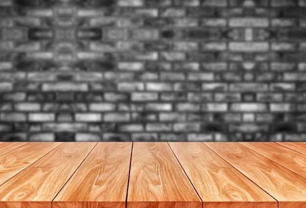 Деревянная таблица перед предпосылкой нерезкости кирпичной стены.
