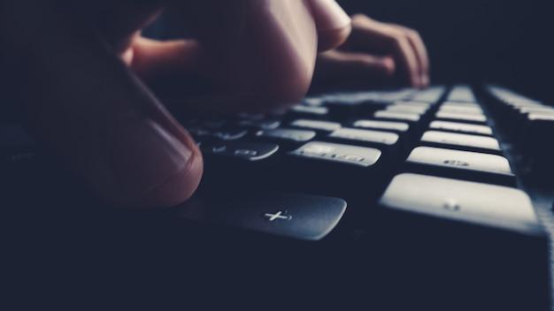 Крупный план мягкого фокуса палец, набрав на клавиатуре.