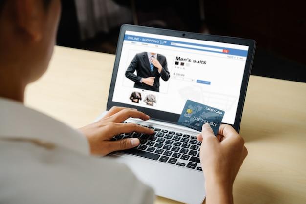 オンラインショッピングにクレジットカードを使用して若い男