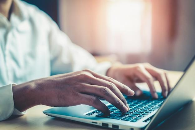 オフィスでラップトップコンピューターを使用して実業家の手。