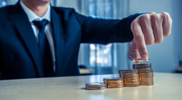Бизнесмен работая с валютой денег монетки.