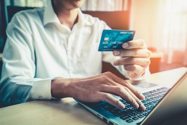 若い男は、オンラインショッピングにクレジットカードを使用します。